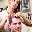 Happy female hairstylist setting client's hair — Stock Photo