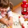 Little girl baking Christmas cookies cutting pastry with a cooki — Stock Photo #36533823