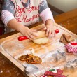 Little girl baking Christmas cookies cutting pastry with a cooki — Stock Photo