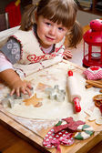 Little girl baking Christmas cookies cutting pastry with a cooki — Φωτογραφία Αρχείου