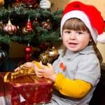 Happy child in Santa hat opening Christmas gift box — Stock Photo