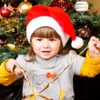 Stock Photo: Happy child in Santa hat opening Christmas gift box