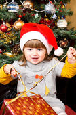 Happy child in Santa hat opening Christmas gift box — Stock Photo