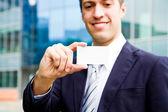 Jovem empresário segurando o cartão de visita na mão e pé na — Foto Stock