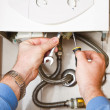 Stock Photo: Plumber at work. Servicing gas boiler