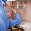 A plumber repairing a broken sink in bathroom — Stock Photo