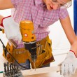 Female carpenter at work using hand drilling machine — Stock Photo