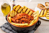 Fish soup with grilled polenta on crock pot — Stock Photo