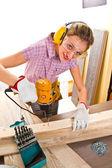 Female carpenter  at work using hand drilling machine — Stock Photo