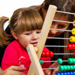 Mother and her little daughter learning math with abacus — Stock Photo