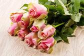 Pink roses isolated on wood background — Stock Photo
