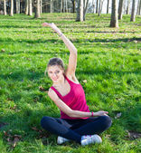Pretty woman doing exercises in the park — Stock Photo