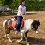 Teenage girl on horseback wearing helmet — Stock Photo #45849047
