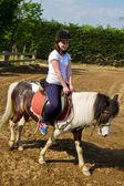 Teenage girl on horseback wearing helmet — Stock Photo