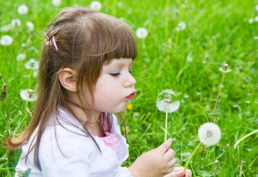 小可爱吹蒲公英的金发小女孩