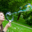 Woman inflating colorful soap bubbles in spring park — Stock Photo