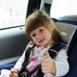 Little cute girl sitting in the car in child safety seat and smi — Stock Photo #45850995