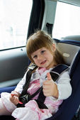 Little cute girl sitting in the car in child safety seat and smi — Foto Stock
