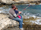 Father and daughter fishing on sea on summer day  — Stock Photo