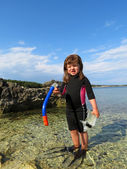Portrait of happy girl with wetsuit, masks and snorkels at the s — Stock Photo