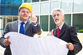Young engineer showing something to his partner at building site — Stock Photo