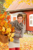 Attractive woman collecting autumn leaves — Stock Photo