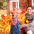 Mother and daughter playinig in autumn leaves - Photo