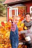 Mother and daughter playinig in autumn leaves — Stock Photo