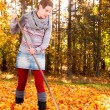 Woman raking vivid yellow autumn leaves — Stock Photo