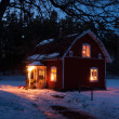 Red painted Swedish wooden house in a wintry landscape at night — Stock Photo