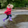 Cute little girl jumping over a puddle — Stock Photo