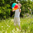 Young boy playing with a ball in a flowering garden — Stock Photo
