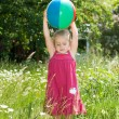 Little girl playing with a ball in a flowering garden — Stock Photo