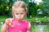 Little girl blowing soa bubbles — Stock Photo