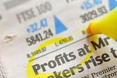 Drawing profits on financial newspaper — Stock Photo