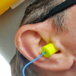 Yellow earplug into the ear — Stock Photo #15754661