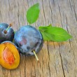 Sweet plum on the old wood - Stock Photo