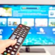 Smart tv and  hand pressing remote control — Foto de Stock