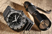 Military watch and flashlight — Stock Photo