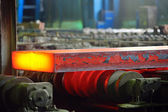 Hot steel on conveyor — Stock Photo