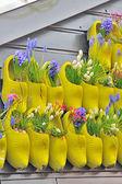 Sapatos de madeira amarelos tradicionais com flores coloridas — Foto Stock