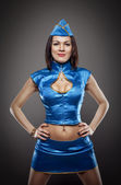 Sexy stewardess in blue uniform studio shot — Stock Photo