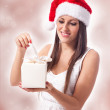 Attractive woman is opening a gift - Stock Photo