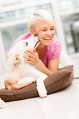 Dog is giving a kiss to a smiling woman — Stock Photo