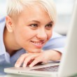 Woman is relaxing in front of her computer while smiling — Stock Photo