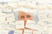 Overwerkte vrouw voor een raam vol met notities — Stockfoto