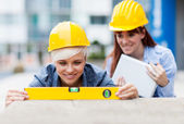 Two Female constructors are working with a level on a wall — Stock Photo