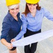 Female constructors holding the project in the hands while smili — Stock Photo #27364539