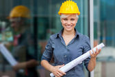Portrait of female constructor with blueprints — Stock Photo