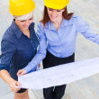 Female constructors holding the project in the hands while smili — Stock Photo
